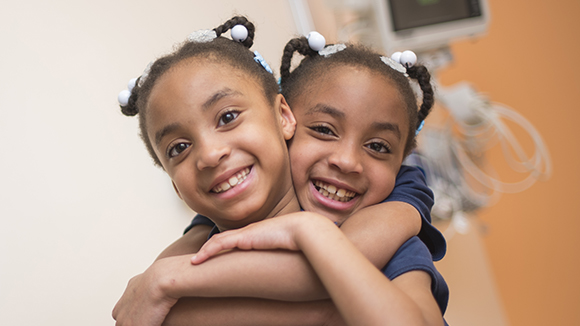 Two young sisters, who are Children's National patients, hug each other and promote sharing your Children's patient journey.