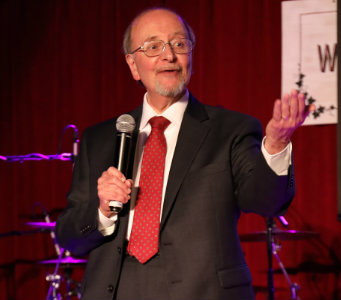 Lawrence D'Angelo, M.D., holds a microphone on stage while speaking.