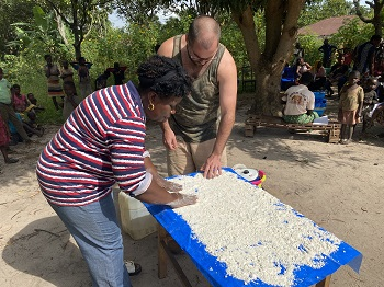 A man and woman spread cassava flour on a tarp to wet it and dry it to release toxins from it before eating.
