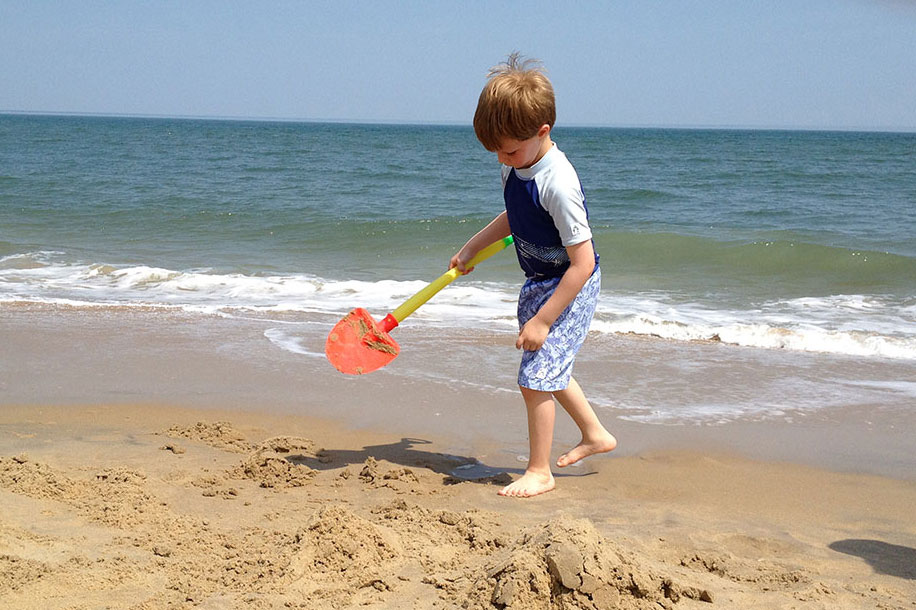 boy with shovel on beach