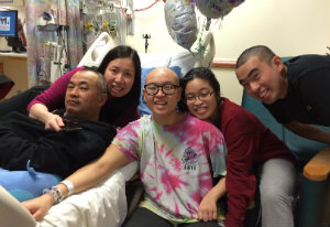 Carly and her family rest in her balloon-filled hospital room