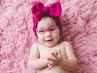 Bella claps her hands while wearing pink eyeglasses and a red hair bow