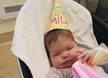 Baby Mila in her stoller with a Happy New Year hat.