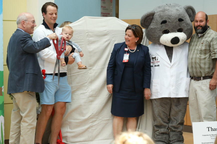 john carlson holds child with dr. bear, kathy gorman and kurt newman smiling nearby