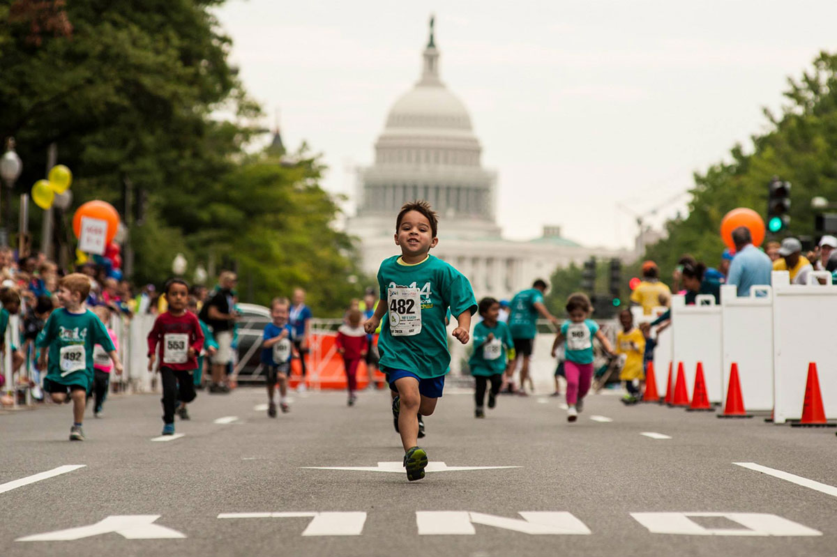 boy running with capitol building in background