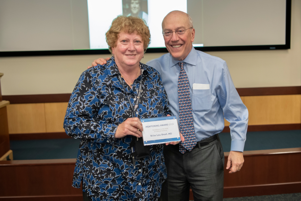 Billie Lou Short, M.D., holds award with CEO Kurt Newman, M.D.