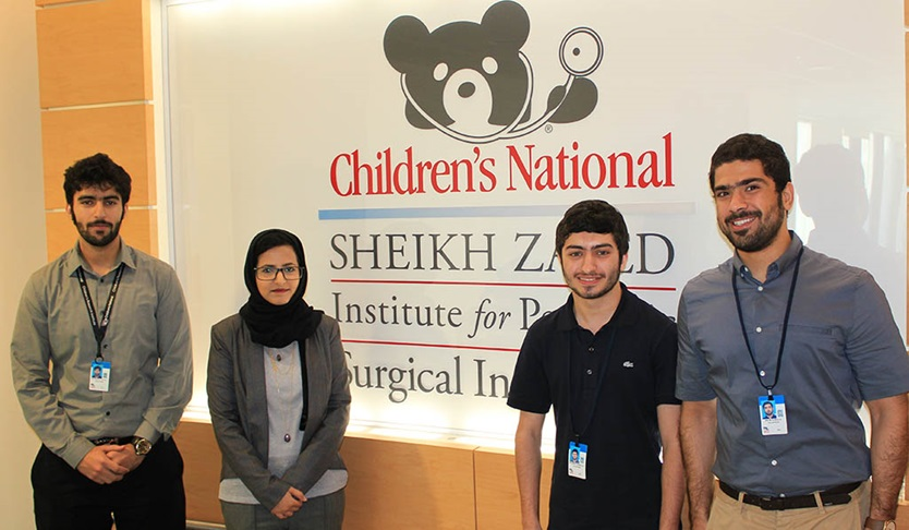 students in front of Sheikh Zayed Institute sign