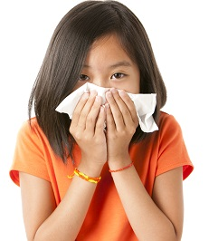 Girl holding a tissue up to her nose and mouth