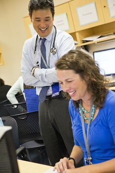 Eugene Wang, M.D., smiles while standing next to a woman he is working with, who is also smiling while sitting at a computer.