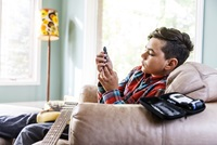 A boy sits on a couch with a guitar in his lap as he tests his own blood sugar level.