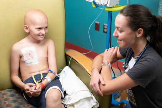 child patient wearing an IV line talks with a squatting female care provider