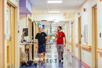 A male nurse helps an adolescent male patient walk down a hospital hallways while the patient is hooked up to a tall wheeled monitor.