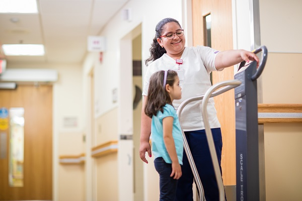 Orthopaedic nurse measures a pre-school aged female patient's weight on a scale.
