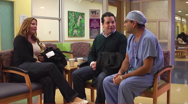 parents and surgeon talk in a waiting room