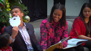 michelle obama first lady and ryan seacrest wearing a santa beart visit in 2016