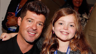 Singer Robin Thicke and a red-haired girl smile for a photo.