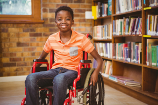 boy in wheelchair in front of bookshelf