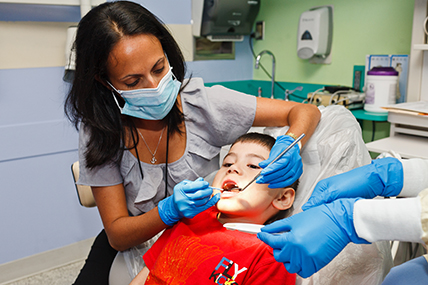 female dentist checks teeth of young patient