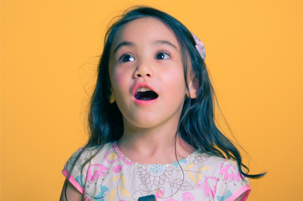 little girl smiles against a yellow background