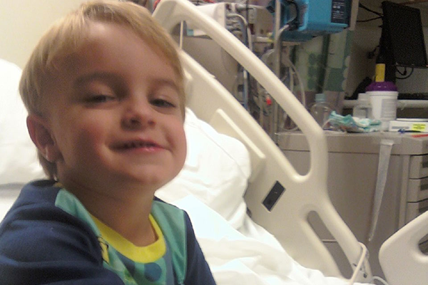 boy smiling on hospital bed